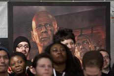 """Поклонники фильма """"Крепкий орешек"""" стоят у постера с актерами Брюсом Уиллисом и Джеем Кортни в Нью-Йорке 13 февраля 2013 года. Новый """"Крепкий орешек"""", вернувший на киноэкраны отважного героя Джона МакКлейна в исполнении Брюса Уиллиса, заработал в свой дебютный уикенд $25 миллионов в США и Канаде, став лидером североамериканского проката. REUTERS/Andrew Kelly"""