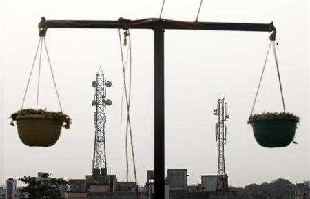 Telecommunication towers are pictured through hanging flower pots at a residential building in Kolkata December 11, 2012. REUTERS/Rupak De Chowdhuri/Files