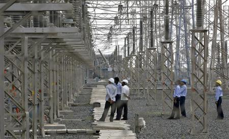 Engineers inspect electric transmission lines at a power plant in Gujarat September 24, 2012. REUTERS/Amit Dave/Files