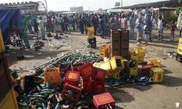 Passanti davanti al luogo dell'esplosione di una bomba in un mercato di Bauchi, nella Nigeria settentrionale. REUTERS/Afolabi Sotunde