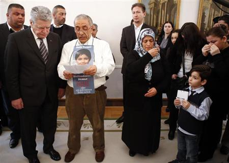 German President Joachim Gauck (L) listens to a statement made by Ismail Yozgat (C), who displays a picture of his son Halit killed by the small neo-Nazi group National Socialist Underground (NSU) in Kassel in 2006, as his wife Ayse (4th L) reacts during a meeting with relatives of the victims at the Presidential residence Bellevue castle in Berlin February 18, 2013. The neo-Nazi group NSU is accused of murdering nine Turkish and Greek immigrants and a policewoman from 2000 to 2007. REUTERS/Fabrizio Bensch