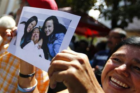 A supporter of Venezuelan President Hugo Chavez holds a copy of a photograph of Chavez released by the Ministry of Information, during a gathering at Plaza Bolivar in Caracas February 15, 2013. Venezuela published the first photos of cancer-stricken Chavez since his surgery in Havana more than two months ago, and said the socialist president was breathing through a tracheal tube and struggling to speak. The two pictures showed the 58-year-old, his face looking swollen but smiling, lying down in a hospital bed and flanked by his two daughters. In one, they were reading Thursday's edition of the Cuban state newspaper Granma. REUTERS/Carlos Garcia Rawlins (VENEZUELA - Tags: POLITICS HEALTH TPX IMAGES OF THE DAY)