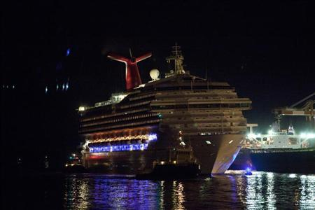 The Carnival Triumph cruise ship is towed towards the dock at the port of Mobile, Alabama, February 14, 2013. REUTERS/ Lyle Ratliff