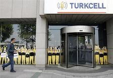 Мужчина проходит мимо головного офиса Turkcell в Стамбуле 14 мая 2009 года. Британский суд через две недели обещает огласить условия, на которых турецкий акционер крупнейшего в стране мобильного оператора Turkcell может вернуть себе пакет, утраченный в ходе акционерного спора с российской Альфа-групп. REUTERS/Osman Orsal