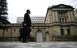 Человек проходит мимо здания Банка Японии в Токио 19 ноября 2012 года. Регуляторы Банка Японии в январе обсуждали покупку долгосрочных государственных облигаций в качестве инструмента монетарной политики, показал протокол заседания банка. REUTERS/Toru Hanai