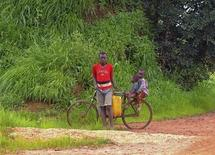 Children are seen with a bicycle on the road outside the village of Tenke, in Congo's copper-producing south, near a smaller hamlet built by the Tenke Fungurume mining operation to rehouse local families displaced by the mine's expansion, January 30, 2013. Katanga, a province roughly the size of Spain, was the heart of central Africa's colonial mining industry, its growth fuelled by Belgium's Union Miniere du Haut Katanga, which produced tonne upon tonne of copper and also the uranium for the atomic bombs dropped on Japan in 1945. Decades of corruption and a brutal civil war brought Katanga to its knees. A period of relative stability since the 2003 peace deal and elections that followed - combined with high metal prices - brought private miners, and officials say Congo's copper exports jumped to 600,000 tonnes in 2012, from under 20,000 a decade ago. Picture taken January 30, 2013. REUTERS/Jonny Hogg