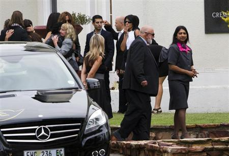 The parents of Reeva Steenkamp, Barry (front, 2nd R) and June Steenkamp (in grey suit, being hugged, on L), arrive at the Victoria Park Crematorium ahead of a memorial service for their daughter in Port Elizabeth February 19, 2013. REUTERS/Rogan Ward