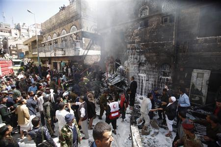Military personnel and fire fighters try to extinguish a fire at the site of an aircraft crash in Sanaa February 19, 2013. A Yemeni fighter jet crashed in the centre of the capital Sanaa on Tuesday, killing at least six people, medical sources said. REUTERS/Khaled Abdullah