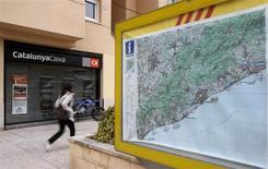 Las pérdidas teóricas de Catalunya Banc y NovaGalicia Banco (NGC) en 2012 ascienden a unos 20.000 millones de euros antes de impuestos, según las estimaciones de Bruselas elaboradas con los planes de reestructuración de las dos entidades nacionalizadas. En la imagen de archivo se puede ver a una mujer pasando ante una sucursal de Catalunya Caixa en la localidad barcelonesa de Vilassar de Mar en noviembre de 2012. REUTERS/Gustau Nacarino