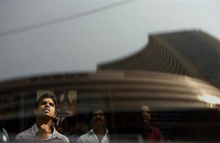 The Bombay Stock Exchange (BSE) building is reflected on a glass window as people look at a large screen displaying Sensex on the facade of the building in Mumbai November 10, 2008. REUTERS/Arko Datta/Files