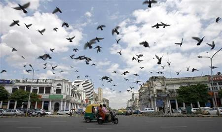 Pigeons fly as clouds gather over New Delhi's Connaught Place July 16, 2009. REUTERS/Buddhika Weerasinghe/Files