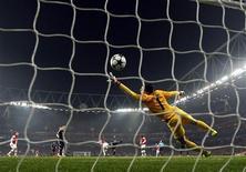 Une frappe du Munichois Toni Kroos trompe le gardien d'Arsenal Wojciech Szczesny. Le Bayern Munich a accompli une grande part du chemin qui le mènera peut-être en quart de finale de la Ligue des champions en allant signer une victoire probante mardi sur la pelouse d'Arsenal (3-1). /Photo prise le 19 février 2013/REUTERS/Eddie Keogh