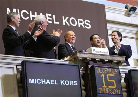 Designer Michael Kors (C) rings the opening bell with guests of Michael Kors Holdings Ltd. at the New York Stock Exchange December 15, 2011. REUTERS/Brendan McDermid