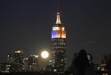 A full moon rises behind the Empire State Building and the skyline of New York, as people watch from a park along the Hudson River in Hoboken, New Jersey, December 28, 2012. REUTERS/Gary Hershorn