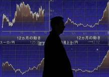 Мужчина проходит мимо информационного табло в Токио, 18 февраля 2013 года. Иена выросла к доллару, так как противоречия между японскими чиновниками поколебали уверенность инвесторов в том, что Банк Японии начнет активное смягчение политики. REUTERS/Yuya Shino