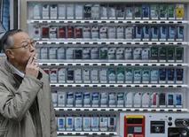Мужчина курит рядом с автоматом по продаже сигарет в Токио 20 февраля 2013 года. Правительство Японии может продать свой $10-миллиардный пакет в третьем по величине в мире производителе табака Japan Tobacco Inc в ближайшие дни, сообщили Рейтер источники, близкие к сделке. REUTERS/Toru Hanai