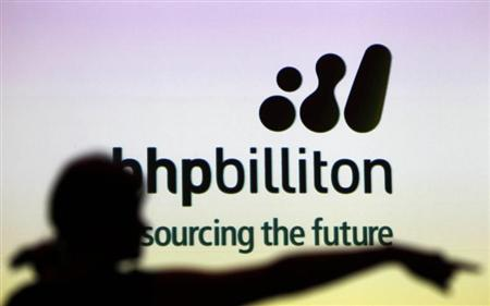 A woman gestures in front of a BHP Billiton sign during a half-year results briefing in Sydney in this February 16, 2011 file photo. REUTERS/Tim Wimborne