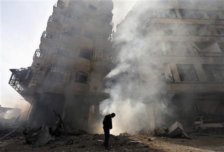 A man walks in front of a burning building after a Syrian Air force air strike in Ain Tarma neighbourhood of Damascus in this January 27, 2013 file photo. REUTERS/Goran Tomasevic/Files