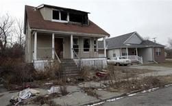A vacant and blighted house sits next to a well-kept occupied house in a once thriving eastside neighborhood in Detroit, Michigan January 23, 2013. REUTERS/Rebecca Cook