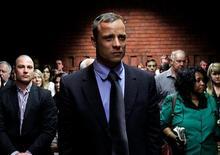 La vista sobre la fianza de la estrella del atletismo paralímpico Oscar Pistorius, acusado de asesinar a su novia, se retomó el miércoles en Pretoria. En la imagen, Oscar Pistorius en el tribunal con su hermano Carl (a la izquierda) al fondo, el 19 de febrero de 2013. REUTERS/Siphiwe Sibeko