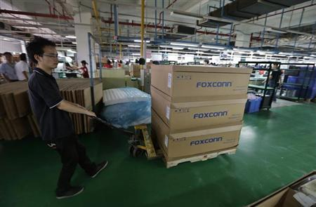 A man pushes a cart loaded with boxes inside a Foxconn factory in Wuhan, Hubei province, August 31, 2012. REUTERS/Stringer/Files