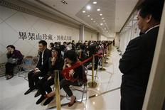 Buyers and property sales agents wait to make deals to buy hotel rooms of Apex Horizon Hotel as individual units from Cheung Kong Holdings, owned by tycoon Li Ka-shing, in Hong Kong February 19, 2013. Just three months after Hong Kong rolled out a tough new round of property cooling measures, home prices have again climbed to record highs with demand unusually strong for new flats over the normally quiet annual Lunar New Year holiday break. Picture taken February 19, 2013. REUTERS/Bobby Yip