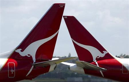 Two Qantas planes pass each other on the runway at Sydney's Kingsford Smith International Airport May 10, 2007. REUTERS/David Gray/Files