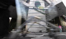 Рабочий толкает тележку для покупок у входа в супермаркет Pao de Acucar в Сан-Паулу 28 июня 2011 года. Французский ритейлер Casino уверен в росте продаж и прибыли в 2013 году после обнародования данных о 29-процентном скачке операционной прибыли за предыдущие 12 месяцев. REUTERS/Nacho Doce