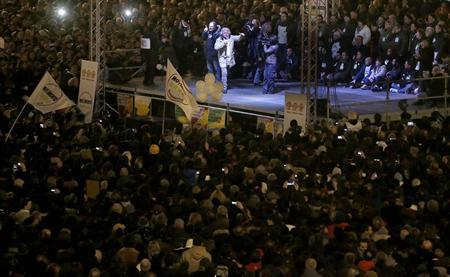 People gather in Duomo Square as Five-Star Movement activist and comedian Beppe Grillo (top C) speaks during a rally in Milan February 19, 2013. REUTERS/Tony Gentile