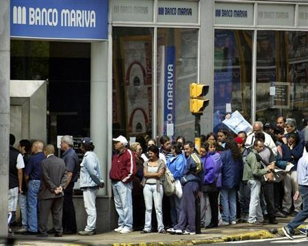 People line up outside a Banco Mariva branch to buy U.S. dollars in the financial district of Buenos Aires, November 15, 2002. REUTERS/Enrique Marcarian EM/ME - RTRDWYT