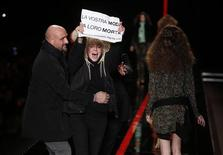 A member of an animal rights organisation holds a sign to protest against the use of animal fur in the fashion industry on the catwalk during the Just Cavalli Autumn/Winter 2013 collection at Milan Fashion Week February 21, 2013. REUTERS/Tony Gentile