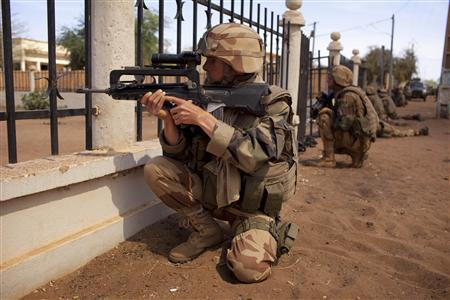 French soldiers take up positions near Independence Plaza, formerly Sharia Square, during fighting with Islamists in Gao, February 21, 2013. French and Malian troops fought Islamists on the streets of Gao and a car bomb exploded in Kidal on Thursday, as fighting showed little sign of abating weeks before France plans to start withdrawing some forces. REUTERS/Joe Penney (MALI - Tags: MILITARY CIVIL UNREST)
