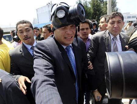 Ecuadorean President Rafael Correa (C) wears a gas mask after striking national policemen released tear gas to keep him inside their main headquarters while he tries to negotiate a solution to the protest over changes in benefits, in Quito September 30, 2010. REUTERS/Guillermo Granja