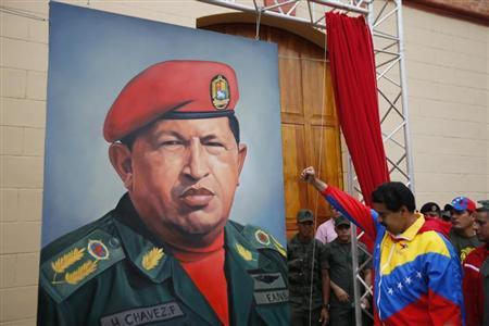Venezuelan Vice President Nicolas Maduro raises his fist next to a painting of President Hugo Chavez during the commemoration of the 21st anniversary of Chavez's attempted coup d'etat in Caracas February 4, 2013. REUTERS/Jorge Silva