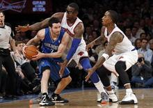 Orlando Magic's guard J.J. Redick (L) looks to pass the ball while being defended by New York Knicks' guard J.R. Smith (R) and Knicks forward Amar'e Stoudemire in the fourth quarter of their NBA basketball game at Madison Square Garden in New York, January 30, 2013. REUTERS/Adam Hunger