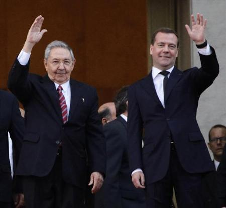 Russia's Prime Minister Dmitry Medvedev and Cuban President Raul Castro (L) wave at the entrance of the Revolution Palace in Havana, February 21, 2013. REUTERS/Desmond Boylan