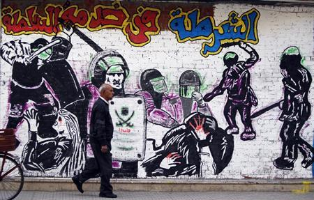 A man walks past graffiti denouncing police violence adorned with the Muslim Brotherhood's logo along Mohamed Mahmoud Street near Tahrir Square in Cairo February 19, 2013. With little regard for the looming economic cliff, politicians in the most populous Arab nation are trading blows over an Islamist-tilted constitution, political violence and an alleged power grab by the Muslim Brotherhood. The words read: ''Police in service for the regime''. REUTERS/Amr Abdallah Dalsh (EGYPT - Tags: POLITICS CIVIL UNREST) - RTR3DZOH