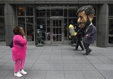 Женщина смотрит на человека, одетого в костюм президента Ирана Махмуда Ахмадинежада, и идущего рядом с ним мужчину, который несет макет ядерной бомбы, в Нью-Йорке, 26 сентября 2012 года. Американские законодатели готовят законопроект, нацеленный на прекращение делового сотрудничества Европейского центробанка и правительства Ирана, в попытке предотвратить использование Тегераном евро для развития ядерной программы, сообщил эксперт Конгресса в четверг. REUTERS/Andrew Kelly