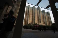 People walk in front of residential towers in Hong Kong February 22, 2013. Hong Kong will impose new measures, including raising buyers' stamp duties, to cool its overheated property sector, which has some of the world's most expensive apartments, officials said on Friday. REUTERS/Bobby Yip