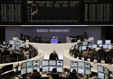 Traders are pictured at their desks in front of the DAX board at the Frankfurt stock exchange February 22, 2013. REUTERS/Remote/Lizza David (GERMANY - Tags: BUSINESS) - RTR3E40A