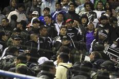 Un grupo de policías bolivianos en medio de los hinchas de Corinthians tras la muerte de un menor en un encuentro de Copa Libertadores de América en Oruro, feb 20 2013. El campeón vigente de la Copa Libertadores de fútbol, el Corinthians de Brasil, deberá jugar sus próximos partidos de local en el torneo a puertas cerradas, después de que sus seguidores fueran acusados de causar la muerte de un hincha boliviano con una bengala, confirmó el viernes la Conmebol. REUTERS/Daniel Rodrigo