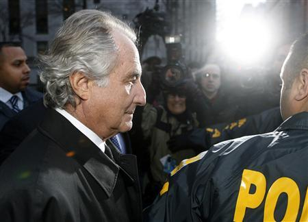 Disgraced financier Bernard Madoff is escorted by police and photographed by the media as he departs U.S. Federal Court after a hearing in New York, January 5, 2009. REUTERS/Lucas Jackson
