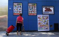 A woman looks at banners with product offers outside a supermarket in Buenos Aires, February 22, 2013. REUTERS/Marcos Brindicci