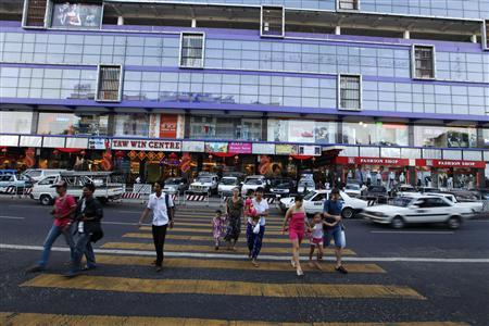 People cross a road after shopping at the newly opened Tawwin shopping centre January 23, 2012. REUTERS/Soe Zeya Tun