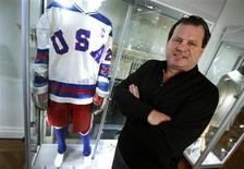 "Mike Eruzione, captain of the 1980 gold medal winning U.S. Olympic ice hockey team poses next to the jersey and uniform he wore when the U.S. defeated the Soviet Union in what is known as the ""Miracle on Ice"" at Heritage Auctions in New York City, February 22, 2013. More than a generation after the 1980 Winter Olympics in Lake Placid, New York, Eruzione is parting with the iconic No. 21 USA jersey, his hockey stick and much of his other Olympic memorabilia in an auction being held by the Dallas-based Heritage Auctions in New York on February 23, the day after the 33rd anniversary of the historic game. REUTERS/Mike Segar"