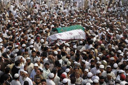 Supporters of Jamiat-Ulema-e-Islam (JUI), one of the largest Sunni political parties, and Ahl-i-Sunnat Wal Jaaat (ASWJ), a political and religious group, carry the caskets of two of their workers who had been gunned down by unidentified gunmen a day earlier, during funeral prayers in Karachi February 19, 2013. REUTERS/Athar Hussain
