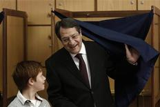 Cyprus presidential candidate Nicos Anastasiades (R), of the right wing Democratic Rally party, leaves a booth as his grandson Andis looks on at a polling station in Limassol February 24, 2013. Cypriots started voting in a runoff on Sunday to elect a president who must clinch a bailout deal for the island nation to avoid a financial meltdown that would revive the euro zone crisis. Conservative leader Anastasiades, who favors hammering out a quick deal with foreign lenders, is favored to win against Communist-backed rival Stavros Malas, who is more wary of the austerity terms accompanying any rescue. REUTERS/Yorgos Karahalis
