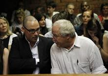 Oscar Pistorius' brother Carl and father Henke await the start of court proceedings in the Pretoria Magistrates court February 20, 2013. REUTERS/Siphiwe Sibeko