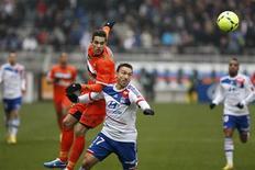 Duel entre Le Lyonnais Steed Malbranque (à droite) et Maxime Barthelme du FC Lorient. L'Olympique lyonnais a rejoint provisoirement le Paris Saint-Germain en tête de la Ligue 1 en s'imposant 3-1 face à Lorient dimanche. /Photo prise le 24 février 2013/REUTERS/Emmanuel Foudrot