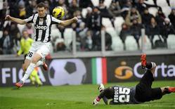 L'attaquant de la Juventus Turin Stephan Lichtsteiner (à gauche) trompe le gardien de Sienne Gianluca Pegolo et ouvre le score. La Juve a conforté sa première place du championnat italien en s'imposant dimanche sur sa pelouse 3-0 face à Sienne. /Photo prise le 24 février 2013/REUTERS/Giorgio Perottino